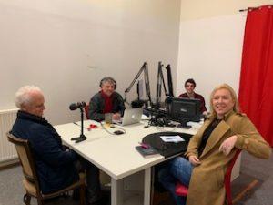 Autour d'une table avec des micros et des ordinateurs, 2 salariés de la radio , Jean Frontin et Adeline coursant sourient et regardent le photographe.