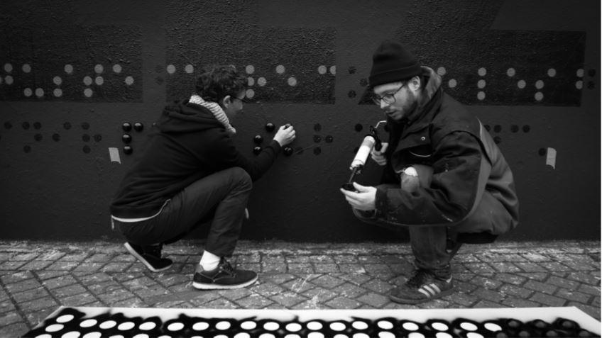 2 jeunes hommes collent des demi-sphères sur un mur.
