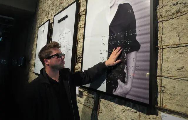 Un homme touche un tableau en braille dans une galerie