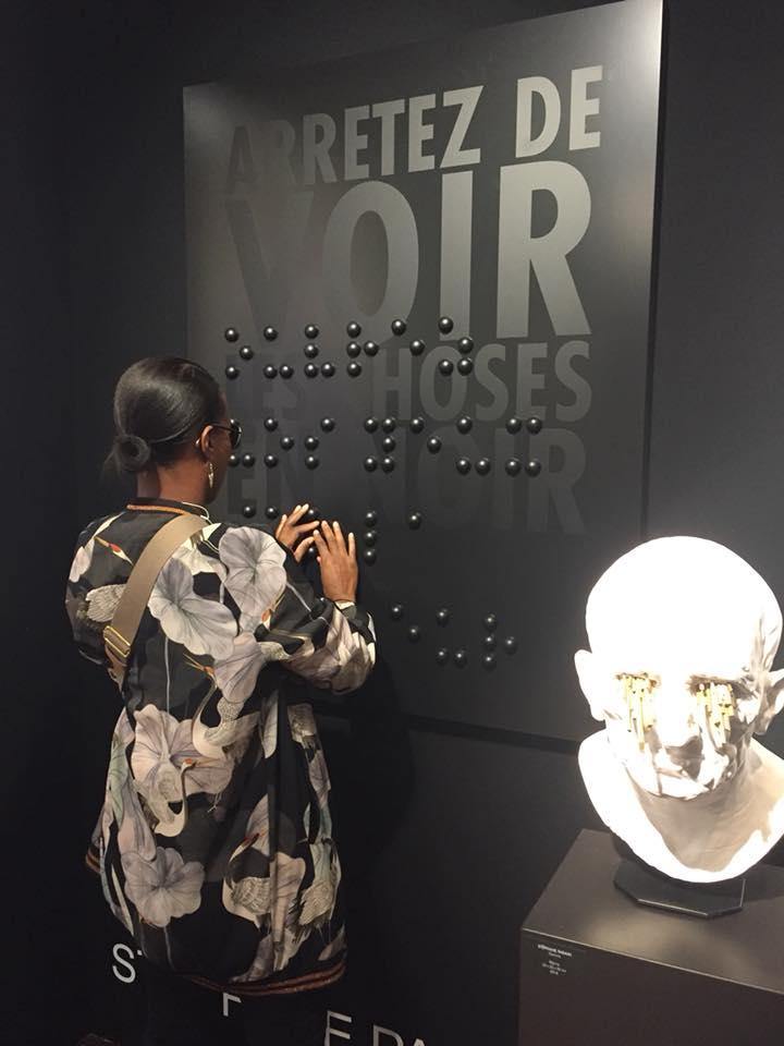 """Une femme lit le relief braille superposé sur l'inscription """"Arrêtez de voir les choses en noir""""."""