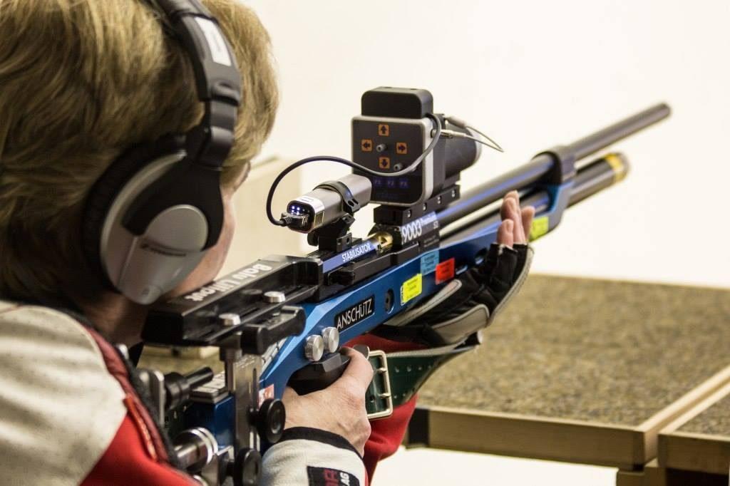 Par dessus l'épaule d'un tireur à la carabine, on découvre l'arme pointée et son système de visée sonore fixé par-dessus.