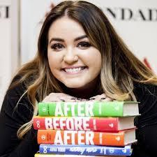La jeune Anna Todd assise de face derrière une table, les mains sur ses livres empilés.