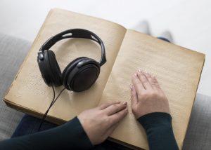 deux mains parcours un livre en braille, un casque audio est posé dessus.
