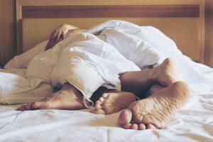 Couple sous la couette d'un lit et vu depuis leurs pieds
