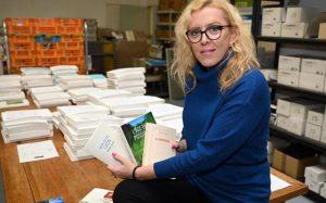 Adeline Coursant présente des livres en braille assise sur le coin d'une table.