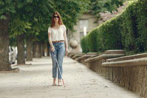 jeune femme de face, dans rue avec canne blanche.