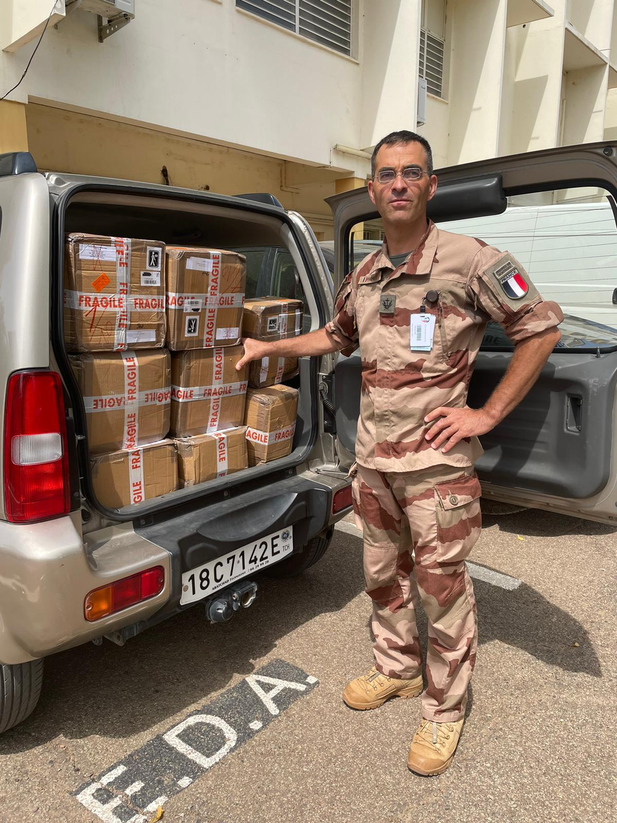 L'aumonier militaire devant un break plein des cartons du don.